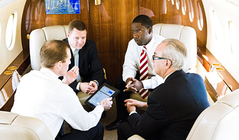 four men with e-tablet in cabin